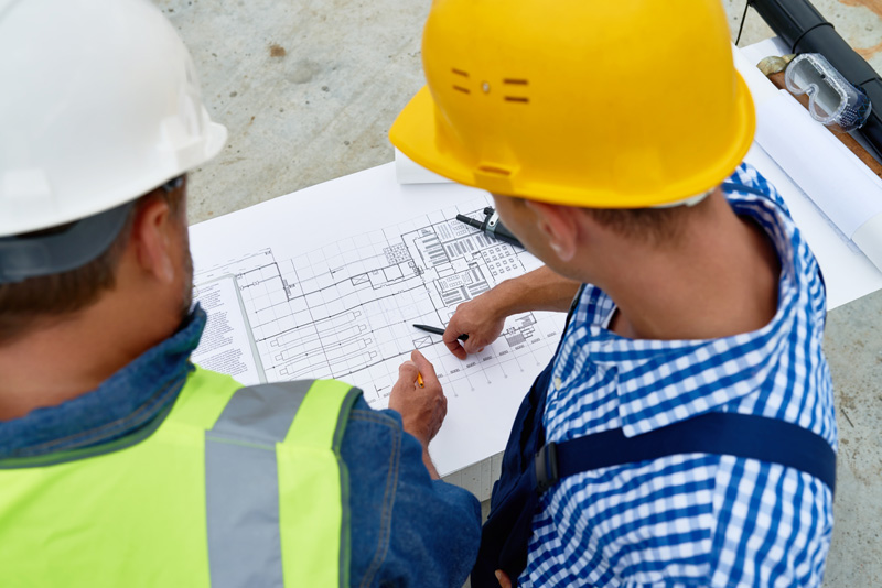 High angle portrait of two construction workers discussing floor plans and engineering documentation on site